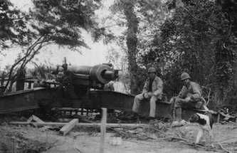 "Rangers 1st Sgt. Leonard ""Len"" Lomell and Staff Sgt. Jack Kuhn sitting on one of the 155mm guns they found and disabled on Pointe du Hoc, June 1944 (Public domain via Battle of Normandy Tours)"