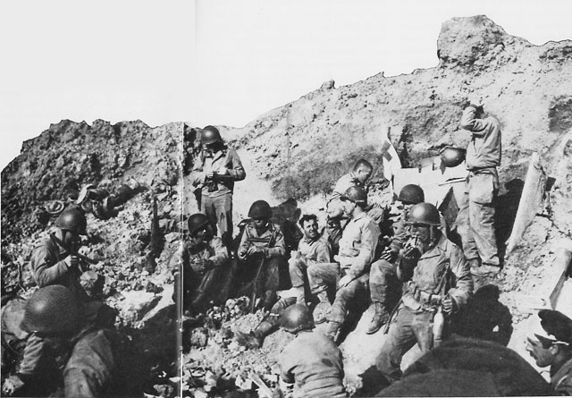 Pointe du Hoc, D-day, 6 June 1944: Lt. Col. James Rudder's Command Post was set in a cratered niche at the edge of the cliff. Lt. Eikner, in charge of the communications section, is near the center, drinking from his canteen (US Navy photo)
