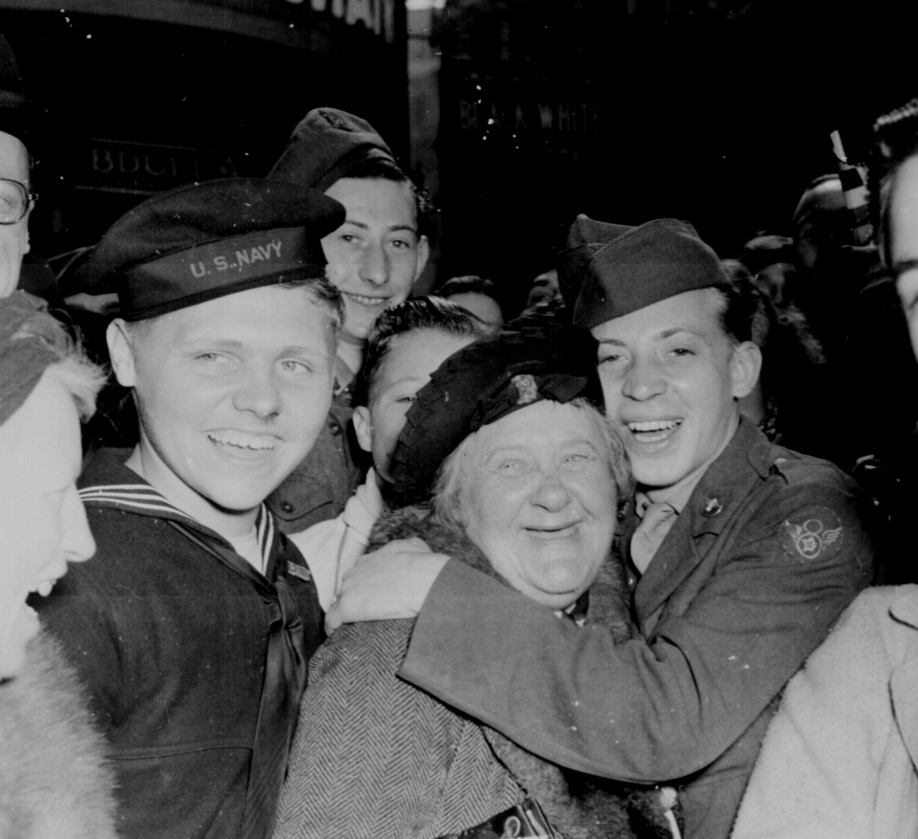 A jubilant American airman hugging an English woman at Piccadilly Circus, London, England, celebrating Germany's unconditional surrender, 7 May 1945 (US National Archives: 111-SC-205398)