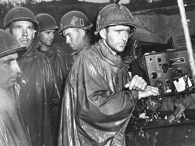 On Okinawa, men of the US 77th Infantry Division listen to the radio report of Germany's surrender on May 8, 1945. One minute after this photo was taken, they returned to their combat posts. US forces on Okinawa celebrated V-E Day by training every ship and shore battery on a Japanese target and firing one shell simultaneously and precisely at midnight. (US National Archives: FA 41224- FA)