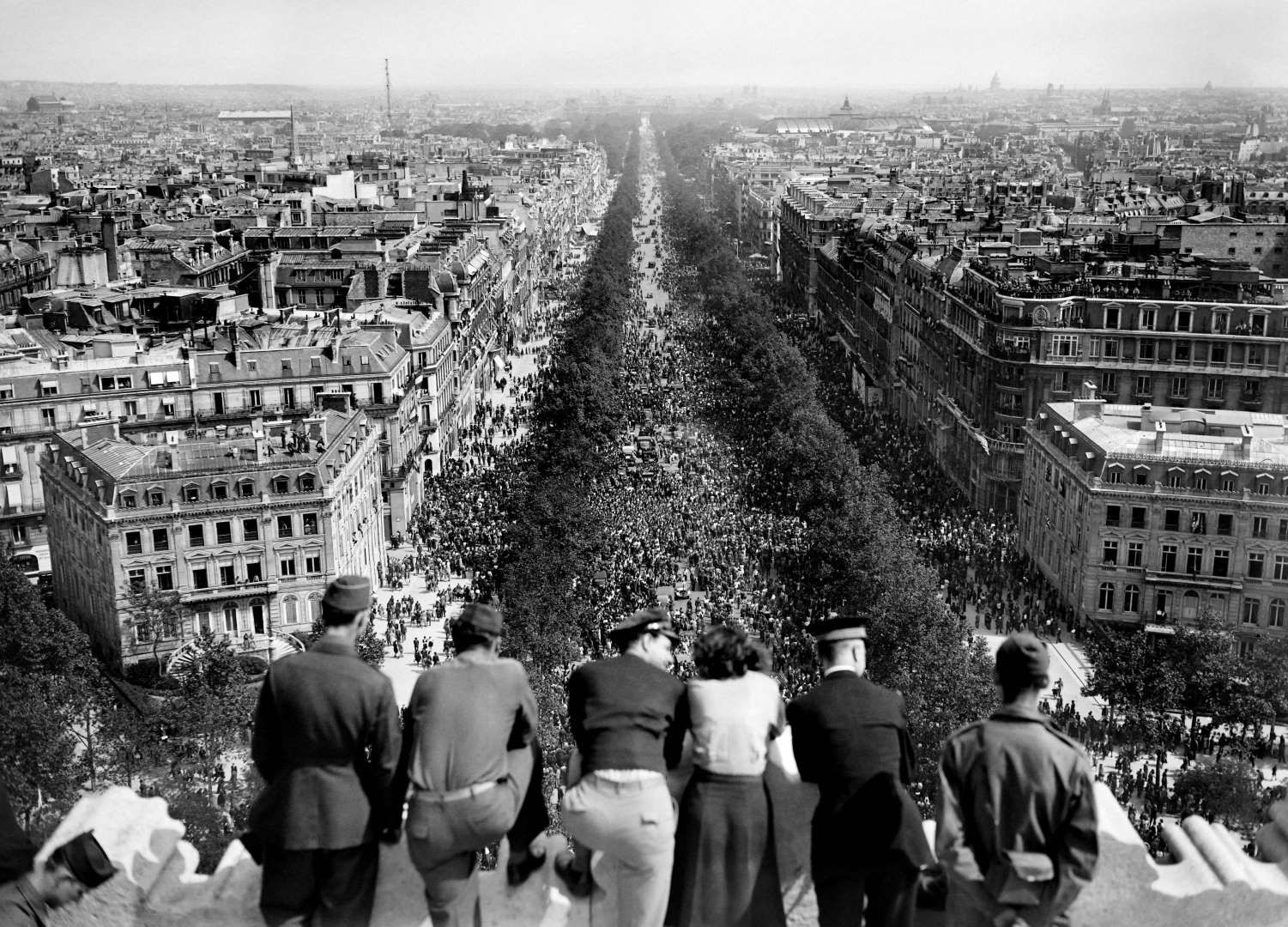 US Army personnel on top of l'Arc de Triomphe in Paris, France watching the celebration in the streets over the war in Europe coming to an end, 8 May 1945 (public domain via WW2 Database)